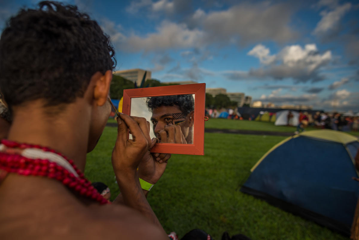 An Indigenous man paints himself at the Free Land Camp, the largest Indigenous mobilisation in the world. © Christian Braga / MNI