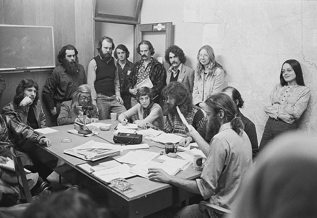 The first public Greenpeace office at 2007 West 4th Avenue in Vancouver, BC, Canada. Bob Hunter sits at the head of the table, Bree Drummond leans against the wall, Rod Marining, with long hair and beard sits to Hunter's right, Alan Clapp stands in the doorway with a file folder, and Henry Payne sits at the far end of the table with a headband. © Greenpeace / Rex Weyler