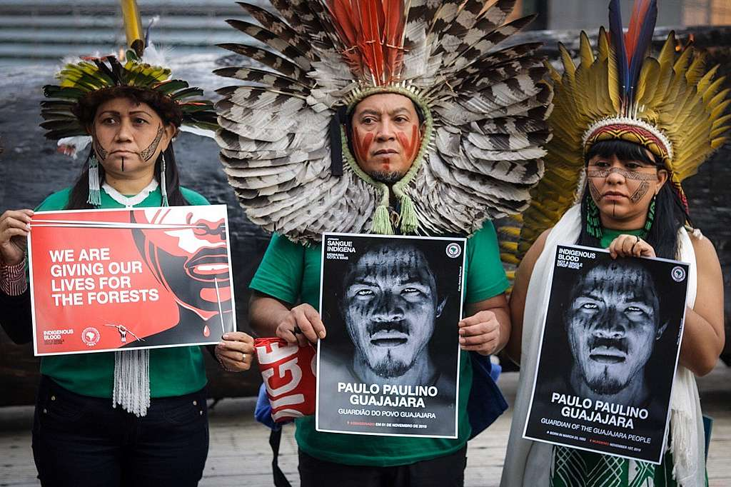 Indigenous Leaders Nara Bare, Kretã Kaygang and Celia Xakriabá hold signs of Paulo Paulino Guajajara in a demonstration in fron of the European Parliament in Brussels, Begium, on November 5th. © Midia Ninja