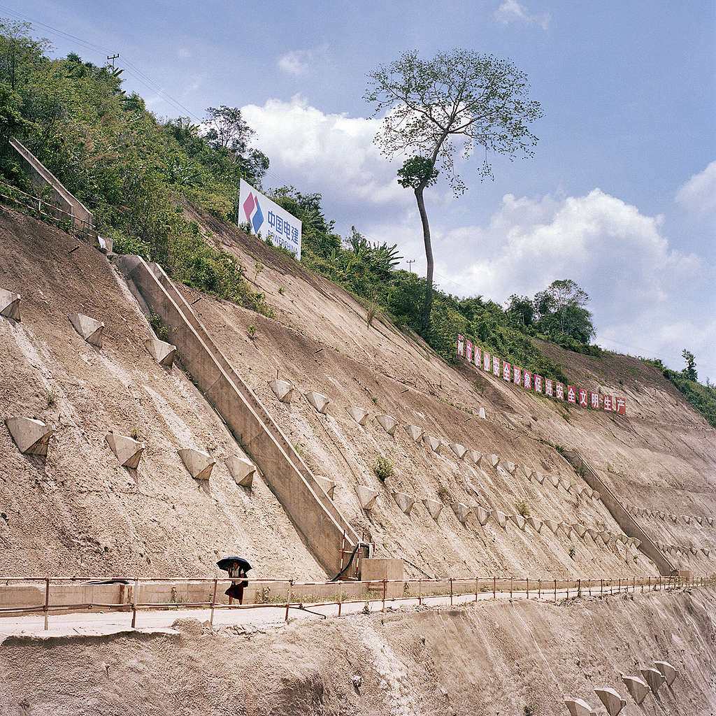 A villager crosses the concrete pavement at Nam Ou River Dam 3 site in Luang Prabang Province on 9 June 2019 in Laos. The Nam Ou dam project is a cascade of 7 dams that spans over 350 kilometres of the Nam Ou River in Laos, an important tributary of the Mekong River. The Chinese funded project is being built over 10 years, with 3 dams currently in operation and the remaining being built. A total estimate of 89 villages will be displaced. The country's environmental and social landscape will be altered in irreversible and disproportionate ways. Ore Huiying