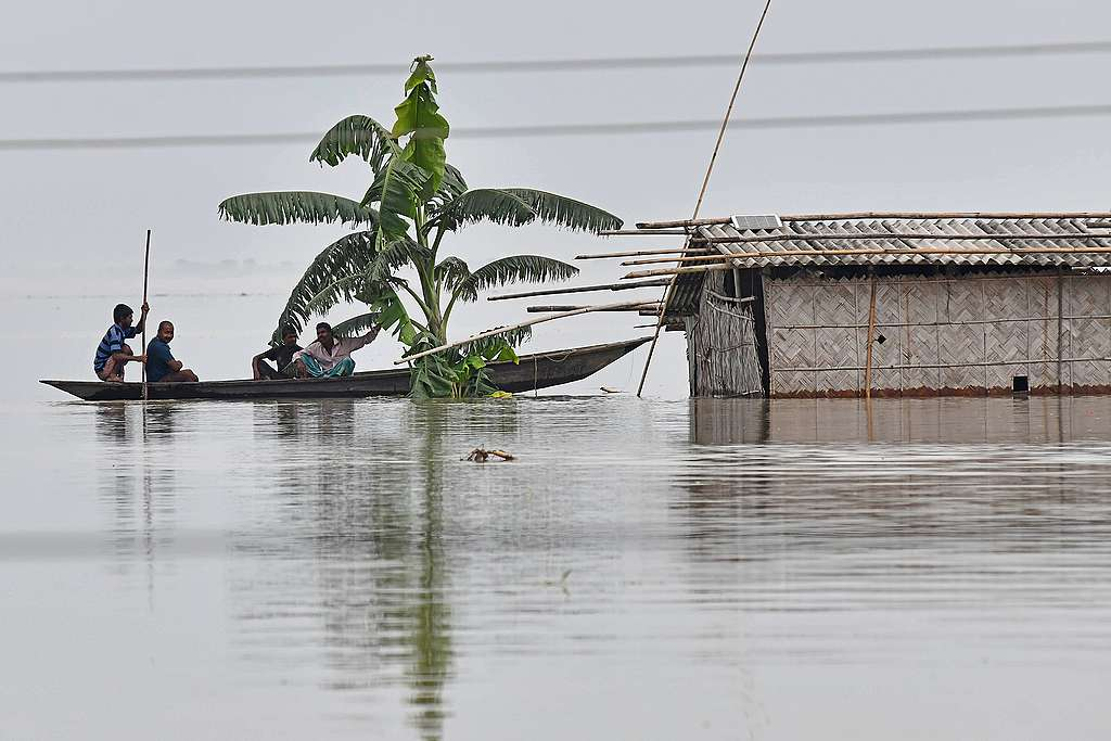 Villagers paddle their boat next to a partially submerged hut in the flood affected area of Hatishila, in Kamrup district of Assam state. © BIJU BORO/AFP via Getty Images