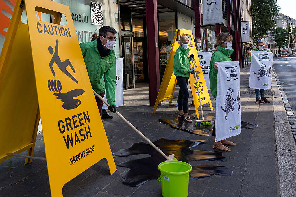 Greenpeace Luxembourg activists use human size yellow slipper floor warning signs and mops to protest continued fossil fuel investment in Luxembourg.
