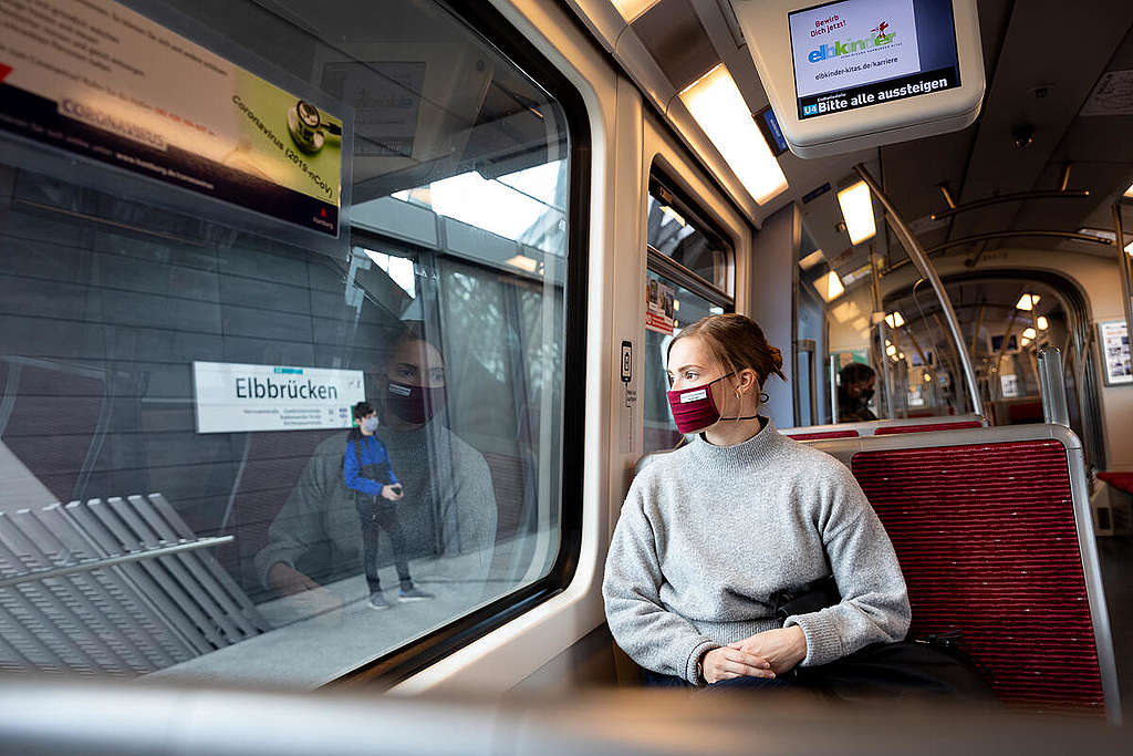 A woman wears a mouth and nose protection mask in public transport.
