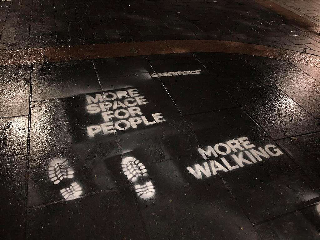 """Greenpeace volunteers in Derby spray green recovery messages. """"More space for people"""" ; """"more walking"""". © Greenpeace"""