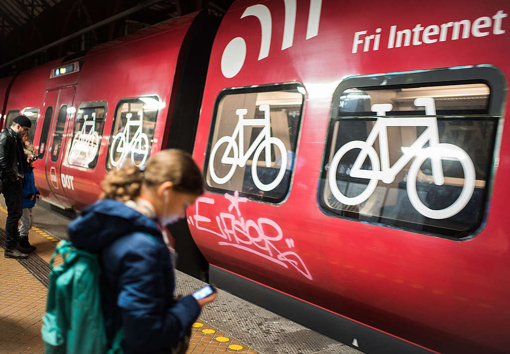 People stand in front of a train with a bicycle Compartment. © Chris Grodotzki / Greenpeace
