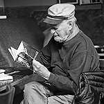 Poet Lawrence Ferlinghetti sits reading a paperback book at Caffe Trieste in 2012. Photo by Cmichel67 / Wikimedia Commons (CC BY-SA 4.0)