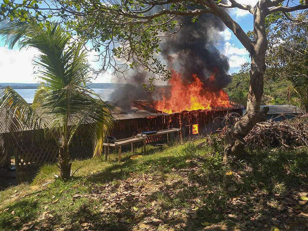 A building burns in a Munduruku village in the Amazon after an attack from illegal miners in May 2021.