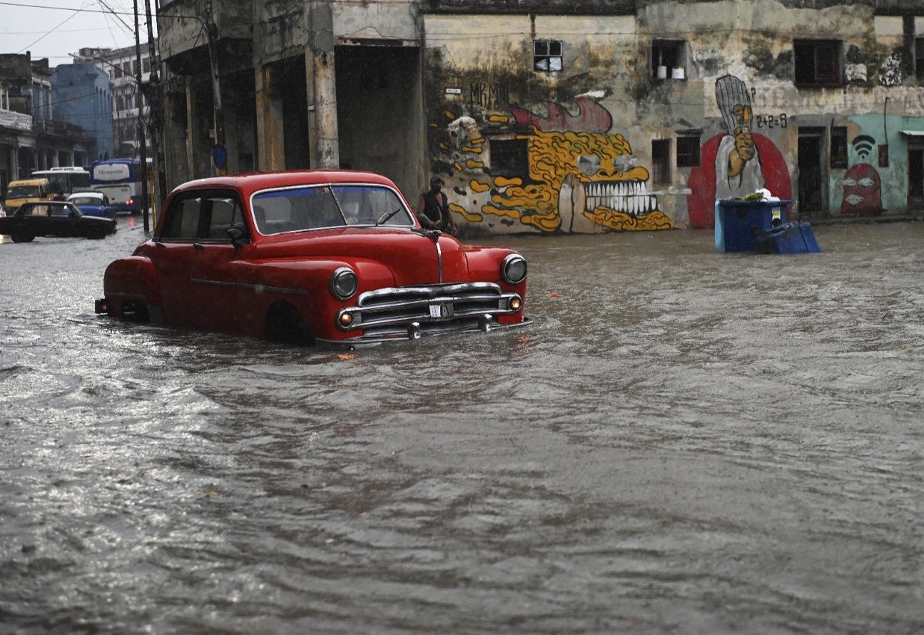 An old American car drives through a flooded street in Havana, Cuba. © Yamil Lage/AFP via Getty Images