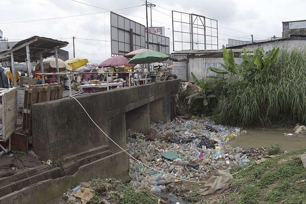 Plastic pollution completely clogging up a stream under a bridge in Dakar neighborhood in Douala, Cameroon
