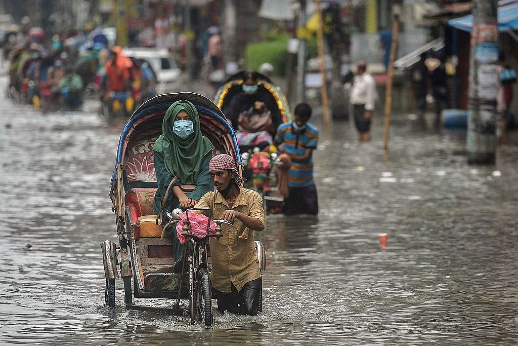 Cycle rickshaw pullers wade through a waterlogged street carrying their passengers after a heavy downpour in Dhaka, Bangladesh. © Munir Uz Zaman/AFP via Getty Images