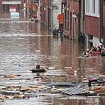 A woman wades her way across a flooded street following heavy rains in Liege.