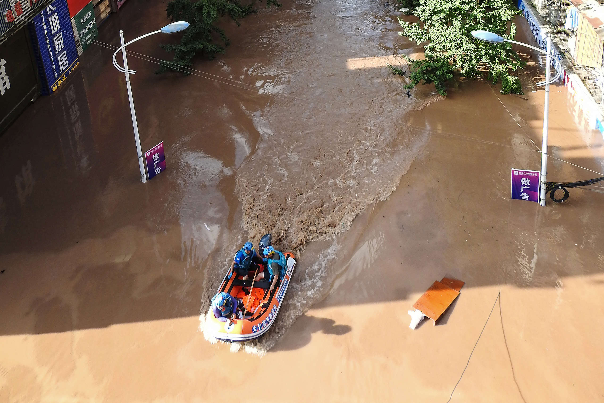 Rescuers looking for stranded residents along a flooded street following heavy rains in Dazhou, China. © STR/AFP via Getty Images