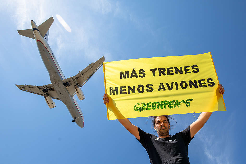 """Greenpeace Spain hold a banner that reads: """"more trains and fewer planes"""". © Greenpeace / Pablo Blázquez"""