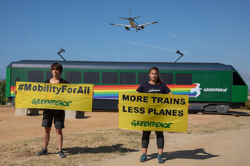 """Activists from Greenpeace Spain hold a banner that reads: """"more trains and fewer planes"""". © Greenpeace / Pablo Blázquez"""