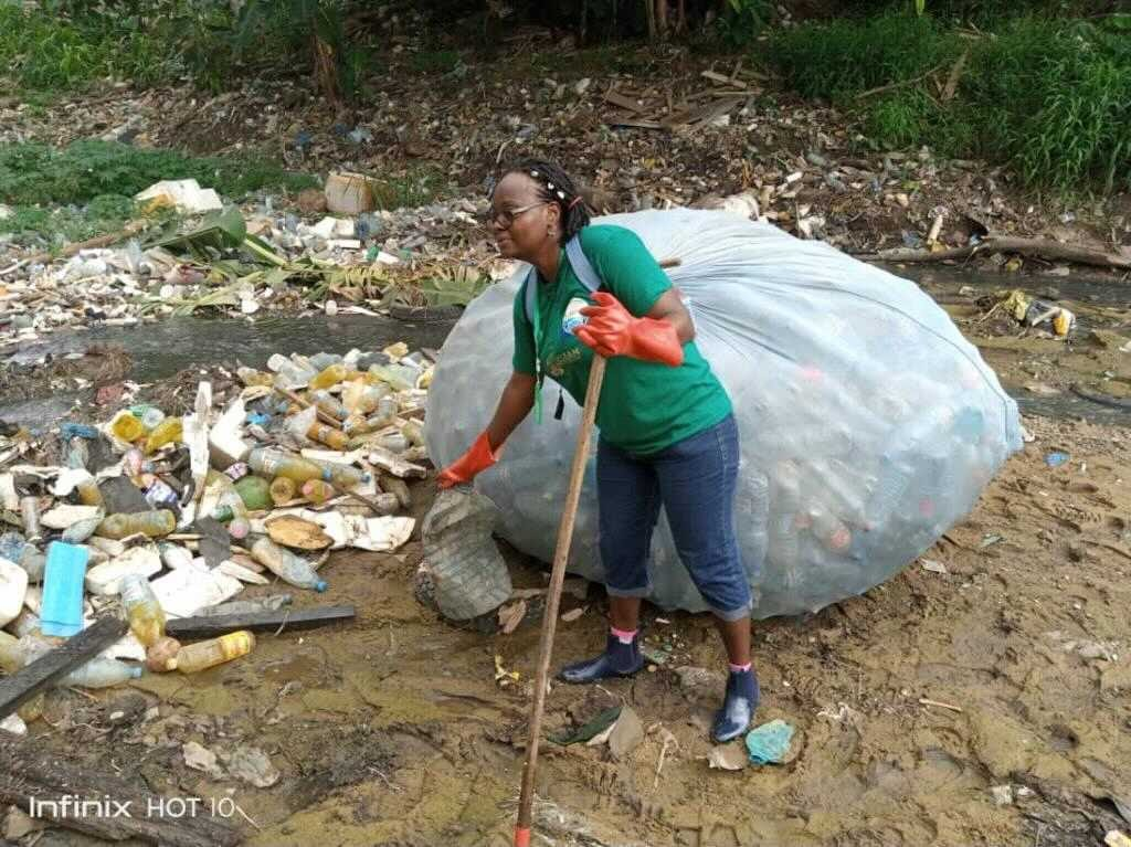 Image showing Nathalie Wamja, a Greenpeace Africa volunteer based in Douala, Cameroon cleaning up plastic and actively fighting against the consequences of plastic pollution and floods.