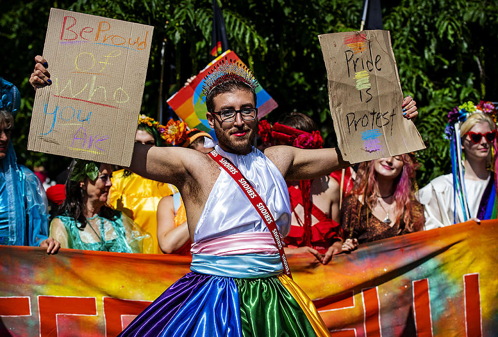 """Picture showing a Queers4Climate activists standing against climate breakdown and holding two signs reading """"Be proud of who you are"""" and """"Pride is Protest""""."""