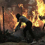 Inhabitants use branches to put out a fire spreading in the Aegean coast city of Oren, Turkey.