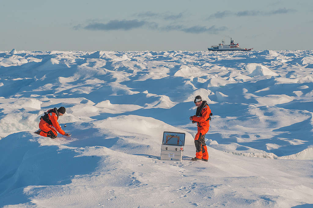 On a stretch of Arctic land completely covered in snow, two people are collecting snow samples.