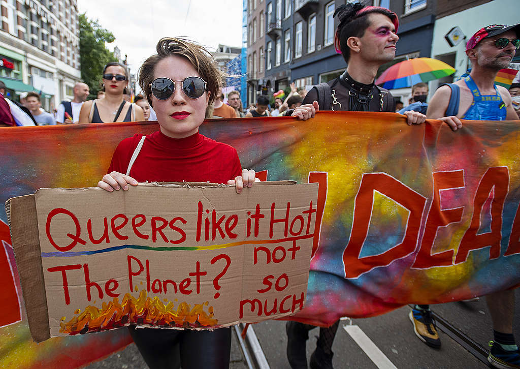 """Picture showing a Queers4Climate activists standing against climate breakdown and holding a sign reading """"Queers like it hot. The planet? Not so much."""""""