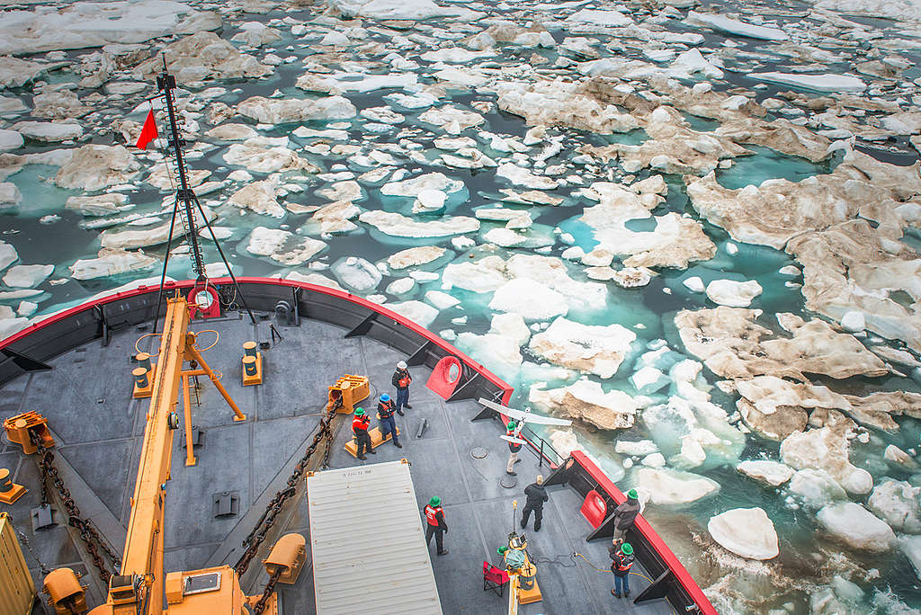 A drone shot of a US Coast Guard ship with men on deck is in Beaufort Sea with floating ice chunks.