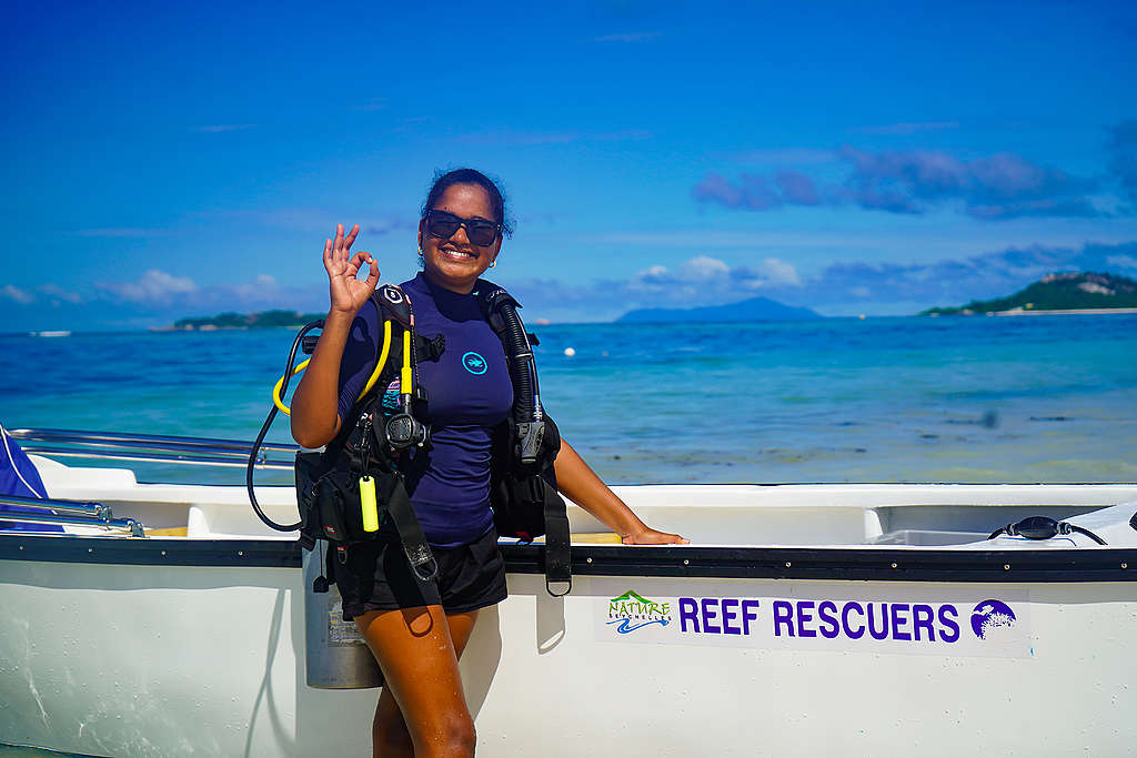25-year old Athina Antoine, sunglasses and dark blue swim top and shorts, has been a part of the Nature Seychelles' Reef Rescuers (white boat) team since 2017