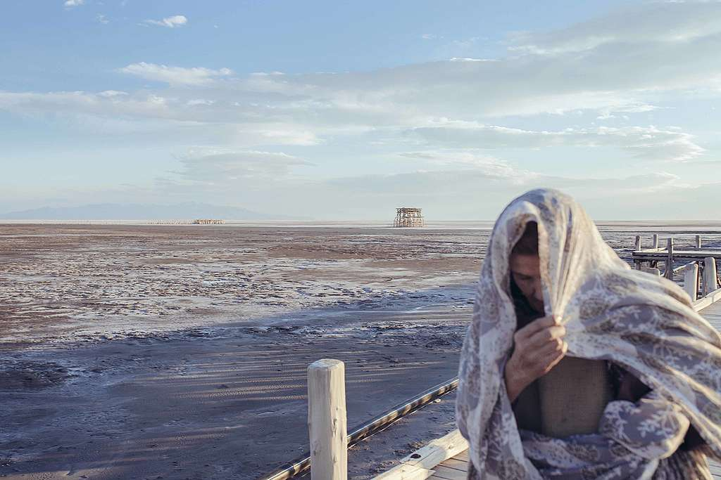 An elderly woman covering her head in a scarf is walking past the coast of a port town in Iran. The lake is very dry and no water is visible.