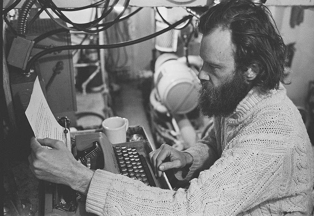 Bob Hunter typing a media release at his engine-room desk, 1976. © Greenpeace / Rex Weyler