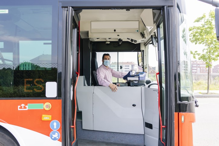 Bus driver wearing protective mask waiting at bus station, Spain.