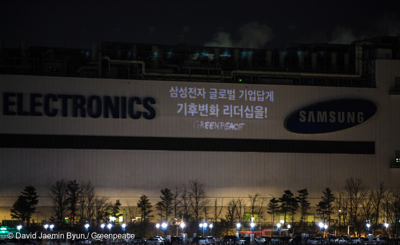 그린피스 활동가들이 2018년 2월, 삼성 기흥 반도체 공장 위에 100% 재생가능에너지 사용을 촉구하는 문구를 프로젝션으로 쏘고 있다.