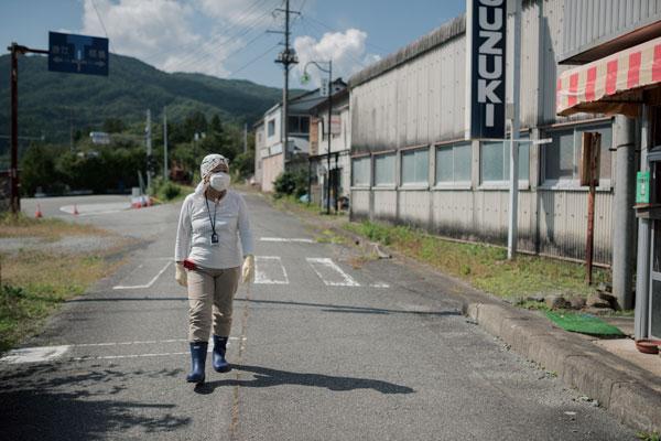 2017년 9월 후쿠시마 사고 피난민인 칸노 미즈에 씨가 후쿠시마현 나미에 지역의 피난구역인 쓰시마 거리를 걷고 있다.