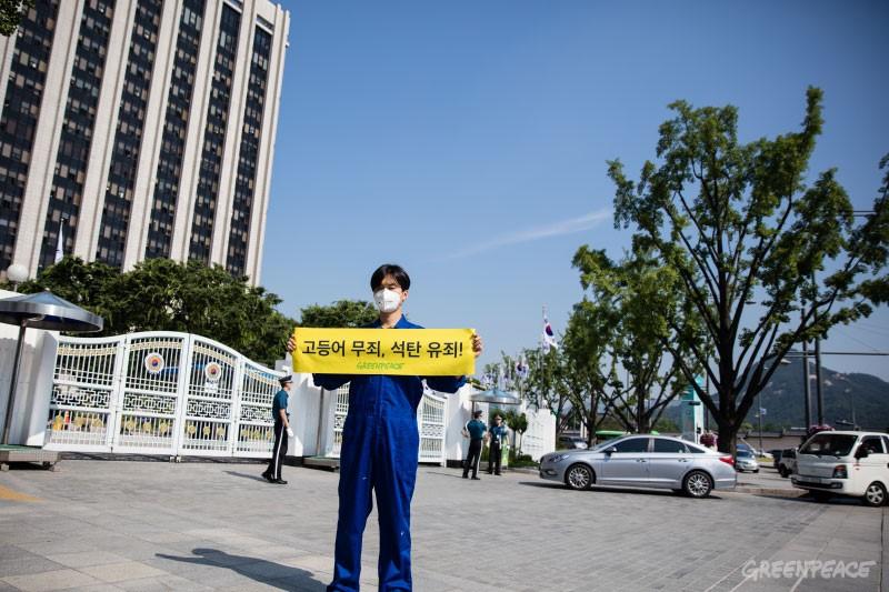 """2016년 6월 3일, 서울 정부청사 앞에서 """"고등어 무죄, 석탄 유죄!""""라는 문구를 들고 있는 그린피스 서울사무소 손민우 캠페이너"""