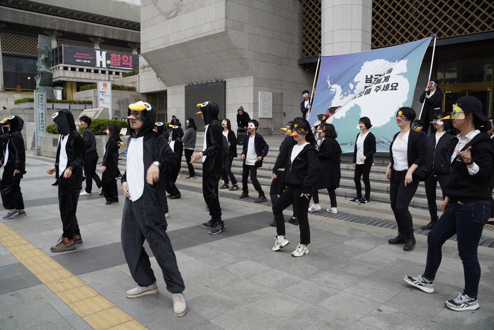 세종문화회관 앞 펭귄 의 모습을 하고 춤을 추고 있는 시민들의 모습