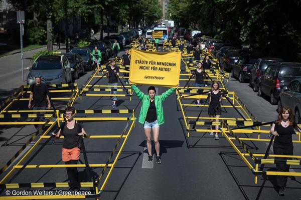 도로의 자동차가 차지하는 공간을 보여주는 행진. 그린피스 활동가가 '차가 아닌 사람을 위한 도시' 라는 사인을 들고 있다