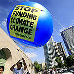 "Greenpeace activists hoist a balloon bearing the message ""STOP FUNDING CLIMATE CHANGE"" at the entrance of the Asian Development Bank Headquarters in Pasig City East of Manila. Greenpeace demands that ADB, Asia's largest institution lender stops supporting fossil fuel and dirty energy projects that cause climate change and inflict harm to thousands of people and instead aggressively fund renewable energy initiatives in the region. The ADB is set to release its energy policy in the next few weeks."