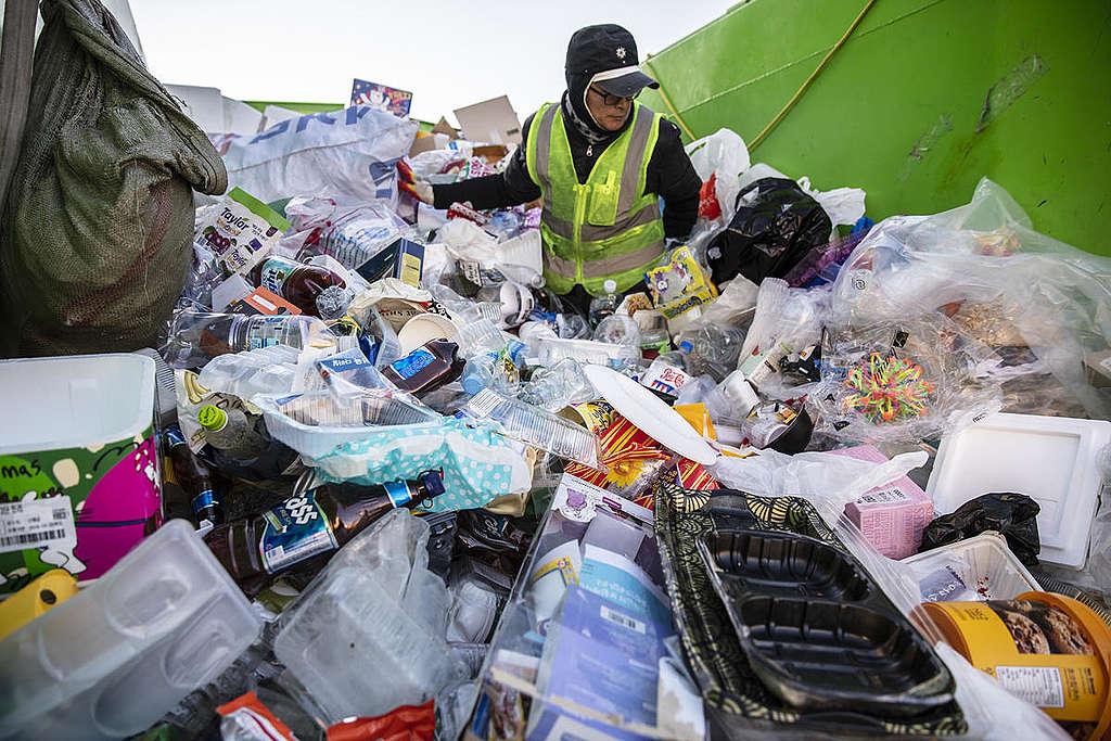 Recolector de basura en medio de una montaña de desechos plásticos.