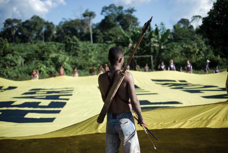 """Comunidades Manduruku con una manta que dice """"Salva el corazón del Amazonas"""""""