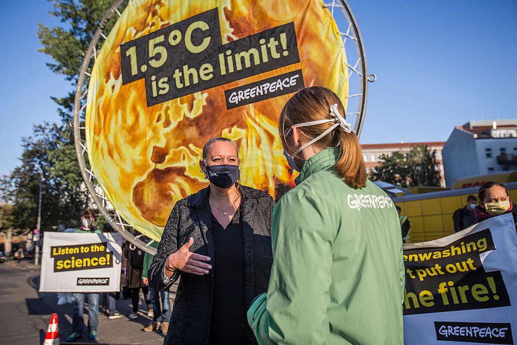 Greenpeace activisten protesteren en gebruiken een 4 meter hoge afbeelding van een brandende aarde om de opwarming voor te stellen. © Sina Niemeyer / Greenpeace