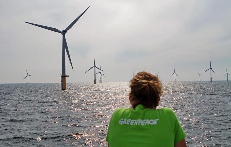 Greenpeace medewerker kijkt naar de windmolens van windpark prinses Amalia. Schone energie leidt tot een reductie van CO2 uitstoot.
