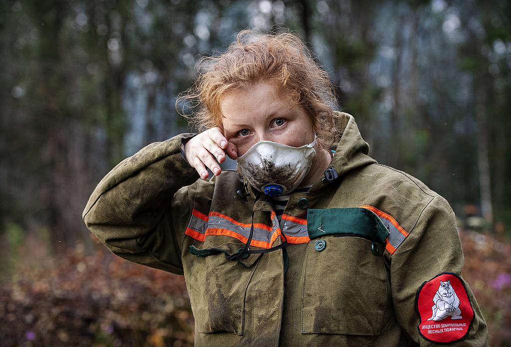 Brandweervrouw vecht tegen de gevolgen van de opwarming van de aarde.