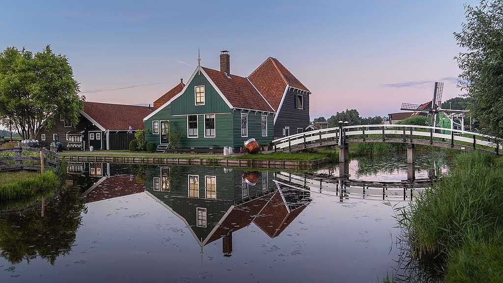 Nederlands huis vlak aan het water. Door de klimaatcrisis stijgt de zeespiegel en kunnen de bewoners last krijgen van overstromingen.