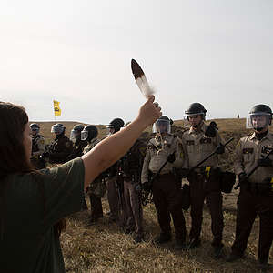 A phalanx of National Guard and police advance toward a water protector holding an eagle feather at a camp near the Standing Rock Reservation in the direct path of the Dakota Access pipeline (DAPL) where 117 people were arrested.