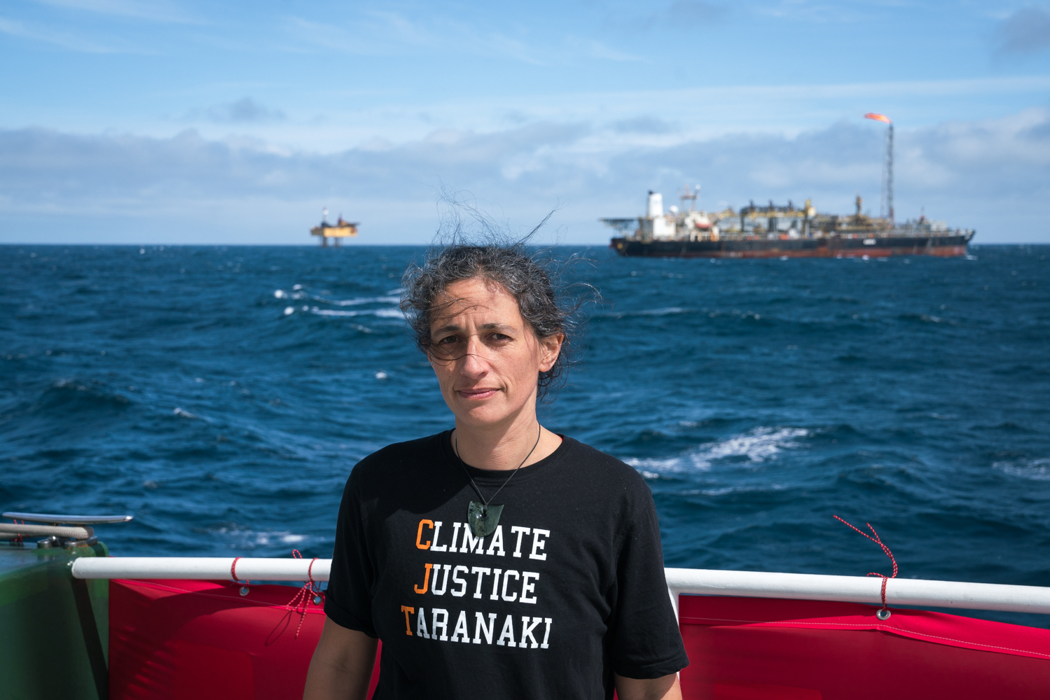 Climate Justice Taranaki member Emily Bailey on the Greenpeace ship Rainbow Warrior with OMV-owned oil drilling platform and oil processing ship in 2018