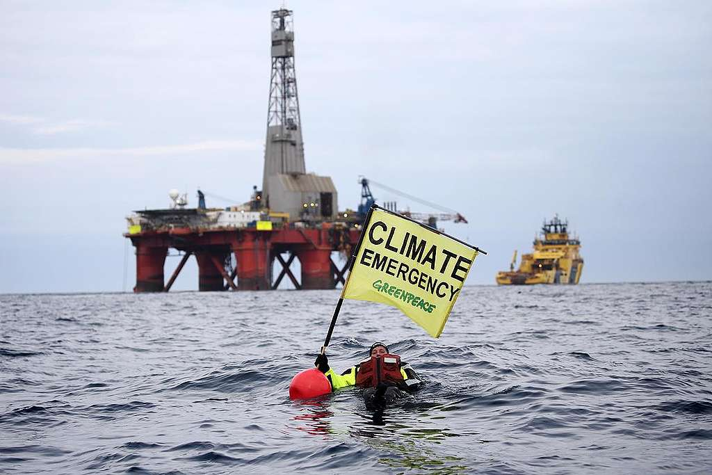 """Greenpeace campaigner Sarah North holds a banner reading """"Climate Emergency"""" whilst floating in front of BP oil rig on day 11 of the protest in the North Sea. Greenpeace is calling on BP to halt drilling for new oil in light of the climate emergency and refocus their business on renewable energy."""