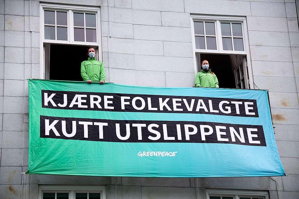 """To Greenpeace-aktivister står i hvert sitt vindu på Grand Hotel i Oslo med et banner med teksten """"Kjære folkevalgte, kutt utslippene"""""""