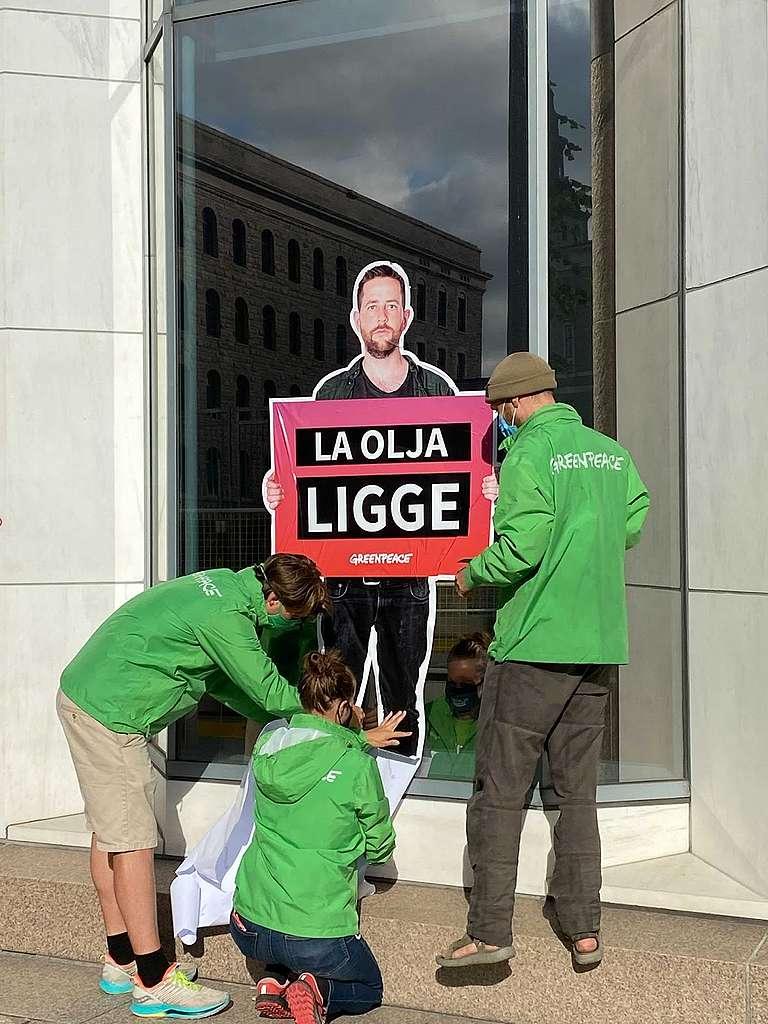 """Aktivister fra Greenpeace klistret opp budskapene """"La olja ligge"""" og """"Norsk olje koker kloden"""" på Olje- og energidepartementets fasade. Foto: Oda Grønbekk"""