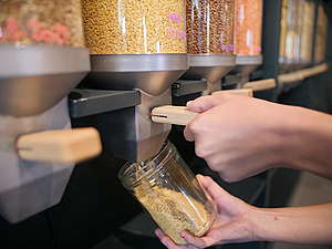 Zero Waste Shop Zurich, container with food, person filling container. © Greenpeace