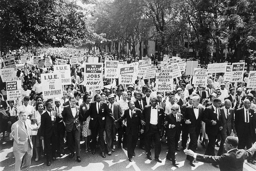 (Original Caption) 8/29/1963-Washington, D.C.- Leaders of the March on Washington lock arms and put hands together as they move along Constitution Avenue here Aug. 28. A. Philip Randolph, march director, is at right, and Roy Wilkins, Executive Secretary of the National Association for the Advancement of Colored People (NAACP), is second from right. The Rev. Martin Luther King, Jr., is seventh from right.