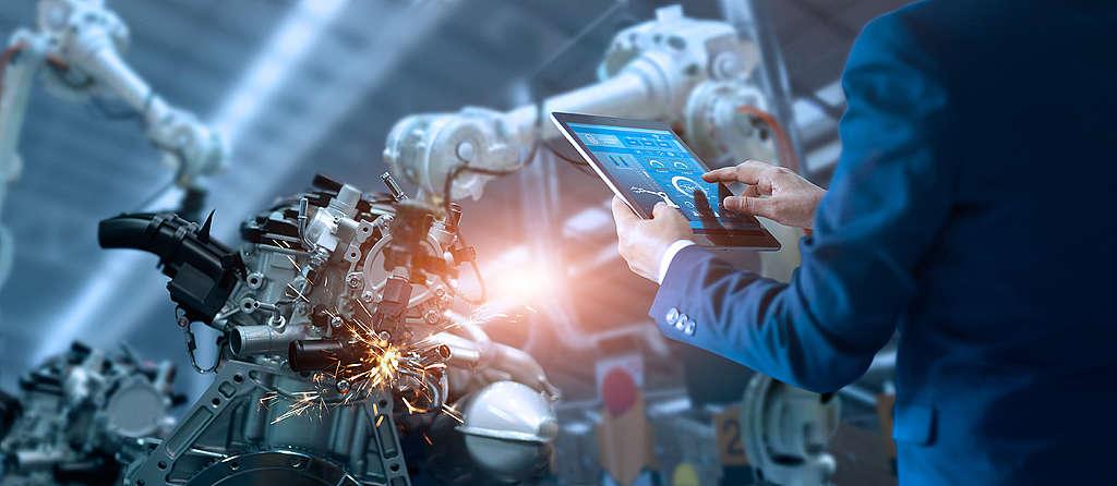 工程師監控自動化機器人手臂機在智能工廠作業。