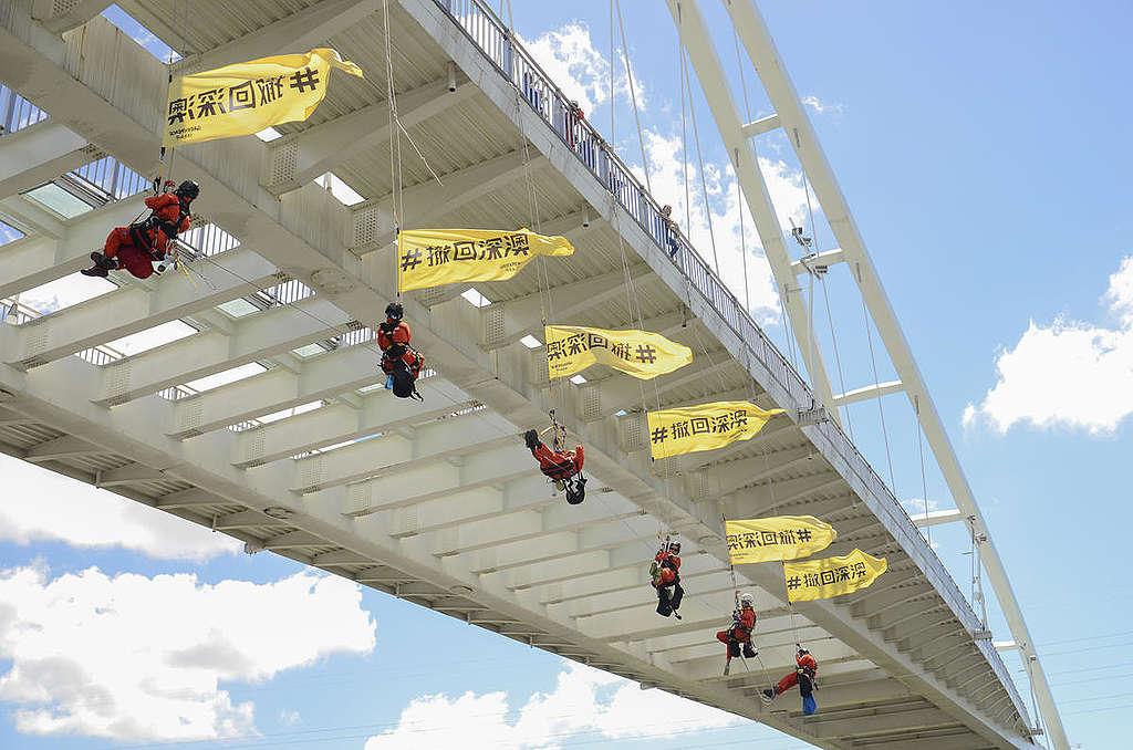 綠色和平行動者在新北市新月橋進行吊掛行動,手持「撤回深澳」布條,要求停止興建燃煤電廠。