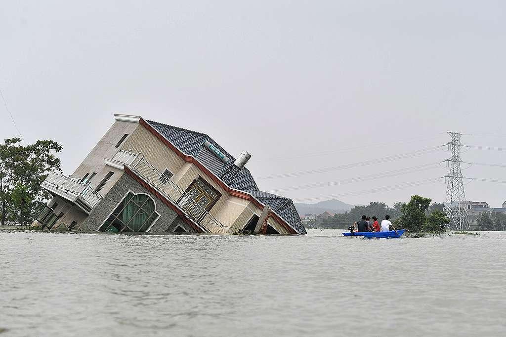 中國中部江西省的暴雨,造成嚴重水患,居民划著小船逃離,行經鄱陽湖附近受損的房屋。從6月2日至7月12日,中國氣象站發布40次豪雨警報。